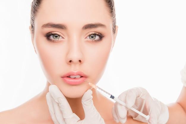 Красивая девушка делает инъекцию, чтобы увеличить губы на белом
