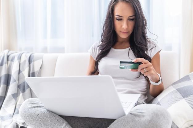 彼女のリビングルームの快適さからオンライン支払いをしている美しい女の子は、彼女の膝の上にラップトップを持って白いソファに座って、そして彼女の手でクレジットカードを見ています。