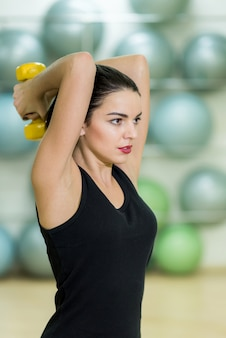 Beautiful girl doing exercise with yellow dumbbell