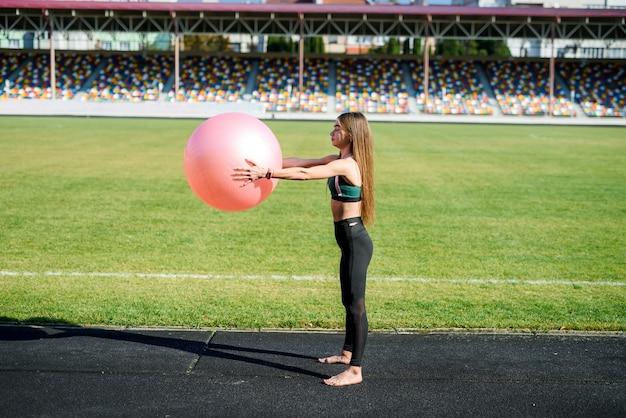 화창한 날에 경기장에서 fitball에 대한 연습을 하 고 아름 다운 소녀. 도시의 건강한 라이프 스타일