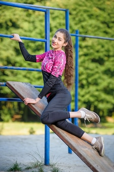 Beautiful girl doing fitness exercises in park. summer time