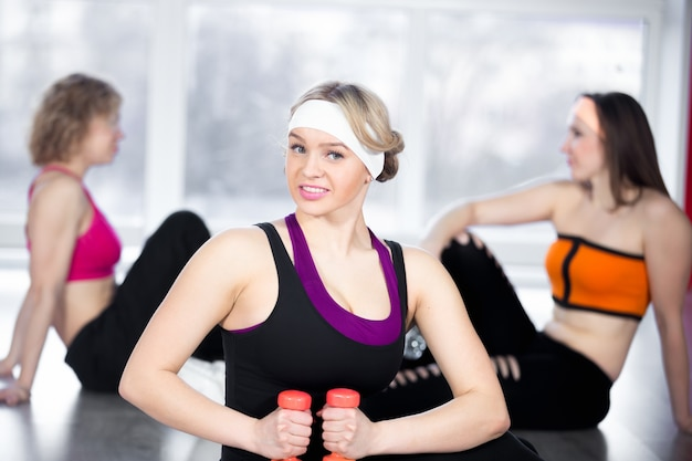 Beautiful girl doing fitness exercises with dumbbells in class
