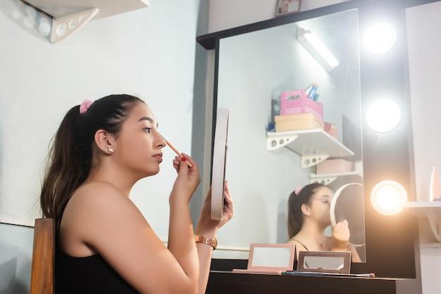 Красивая девушка делает макияж с зеркалом в своей комнате.