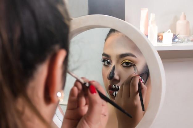 Красивая девушка делает макияж зубов черепа на хэллоуин с ее маленьким зеркалом в своей комнате.