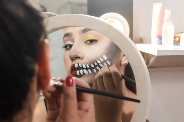 Красивая девушка делает макияж зубов черепа на хэллоуин в своей комнате.