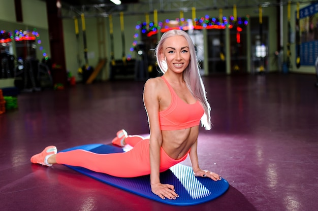 Beautiful girl doing stretching at the gym.
