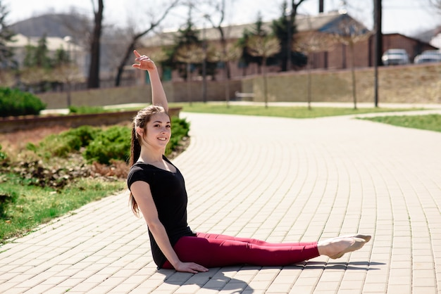 Beautiful girl doing stretching on nature.
