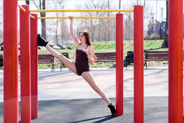 Красивая девушка делает растяжку на спортивном поле Premium Фотографии