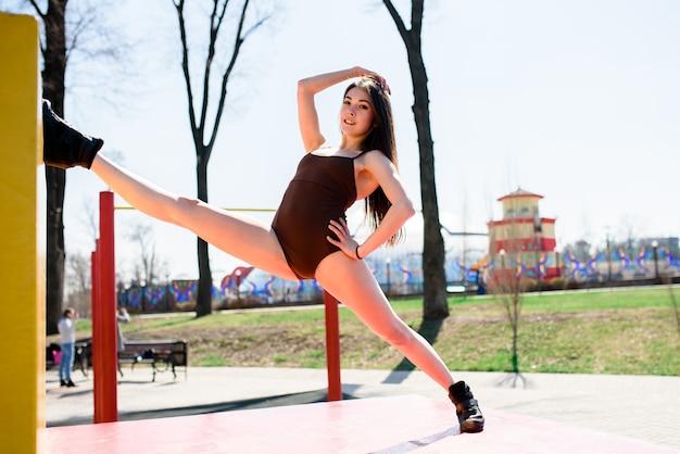 Красивая девушка делает растяжку на спортивном поле