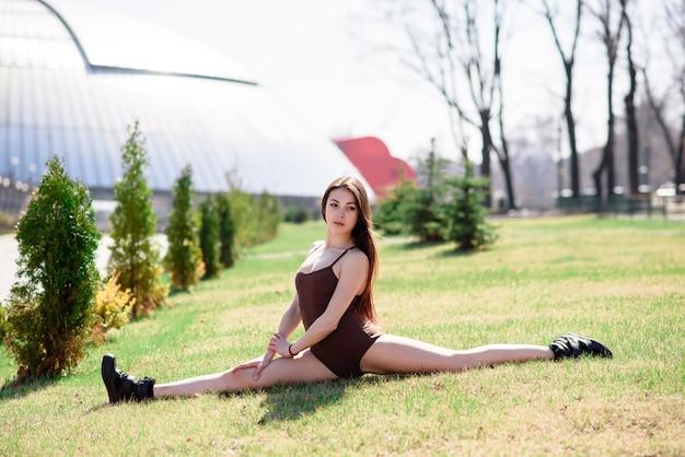 Красивая девушка делает растяжки на природе. Premium Фотографии