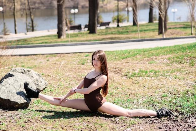 Красивая девушка делает растяжку на природе.