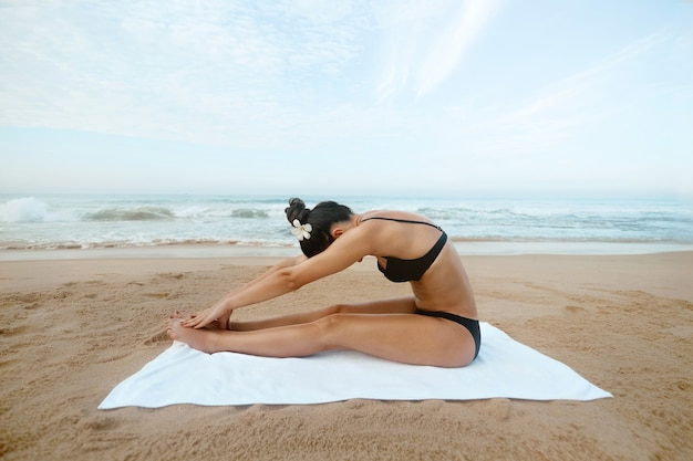 Beautiful girl doing yoga training. fitness female athlete relaxing on beach doing a warm-up.