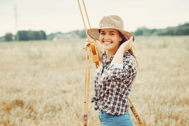 Beautiful girl drawing in a field