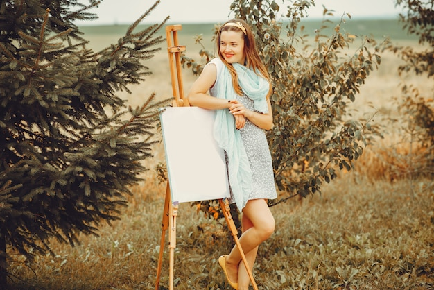 Beautiful girl drawing in a field