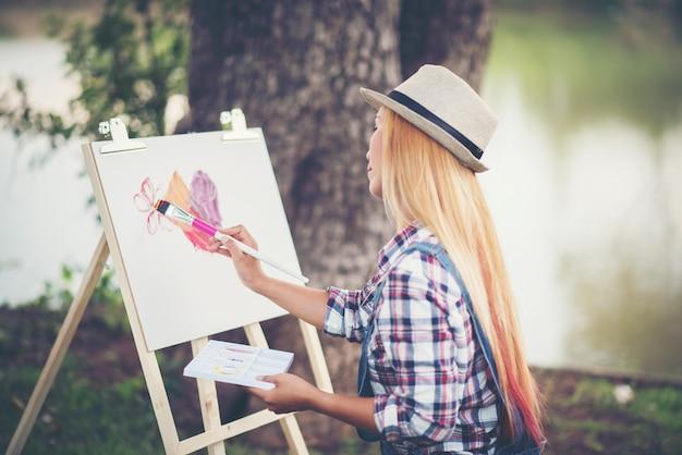 Красивая девушка рисует картину в парке