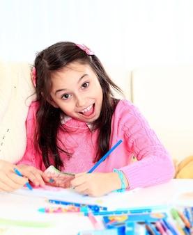 美しい少女は彼女の顔に驚きと喜びを持ってクレヨンとマーカーで描きます