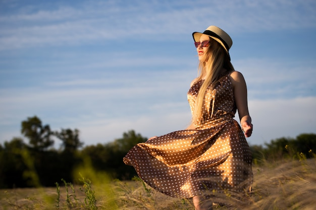 Beautiful girl in dress and hat on the field in the setting sun.