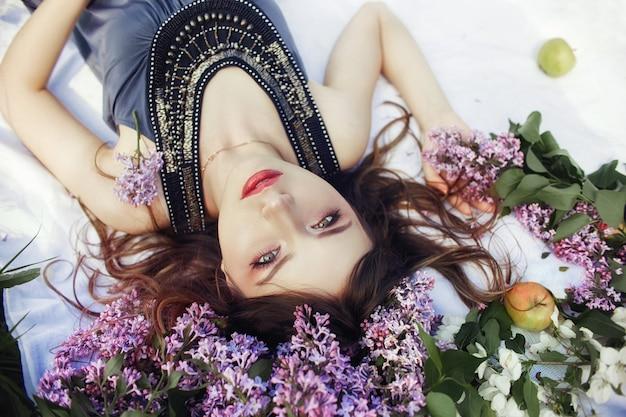 Beautiful girl dress lying lilac branches summer