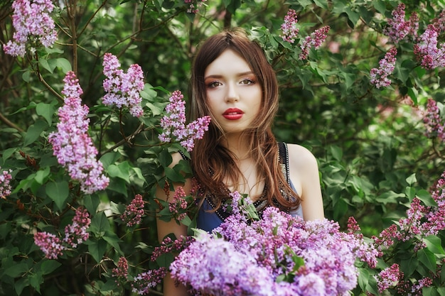 Beautiful girl in a dress posing in bush of lilacs