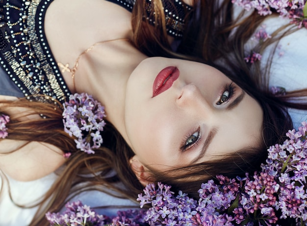 Beautiful girl dress posing lying lilac branches