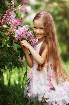 Beautiful girl in dress posing near bush of lilacs