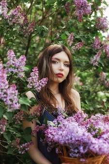 Beautiful girl in a dress posing near bush lilacs