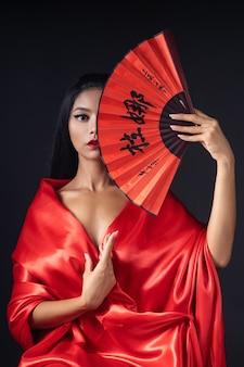 팬과 함께 빨간 기모노에서 게이샤로 옷을 입고 아름다운 소녀
