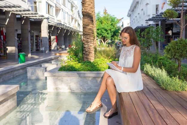 Красивая девушка, одетая в белое платье и солнцезащитные очки, планируя рабочий процесс и делая заметки в блокноте на летней улице.