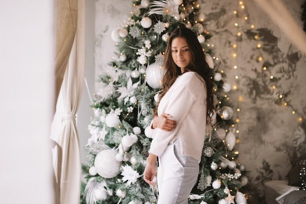하얀 스웨터와 바지를 입은 아름다운 소녀는 아늑한 장식된 방의 창문 앞에 있는 새해 나무 옆에 서 있습니다.