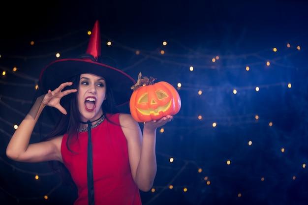 Красивая девушка, одетая в красный костюм, как ведьма, держащая резную тыкву на вечеринке в честь хэллоуина.