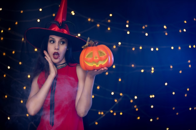 Beautiful girl dressed up in red costume like a witch holding carved pumpkin in halloween party.