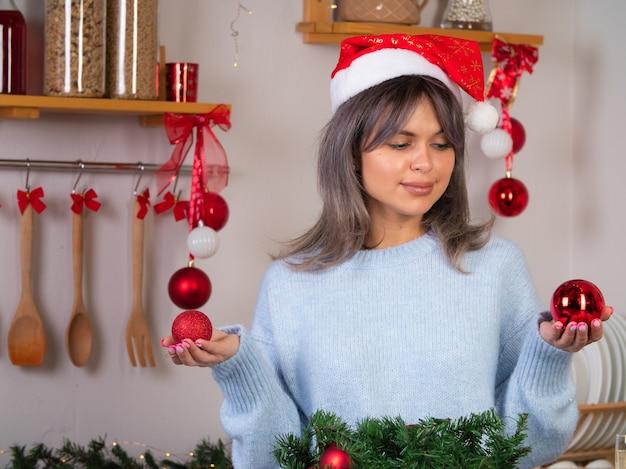 美しい少女はクリスマスのためにクリスマスツリーをドレスアップ