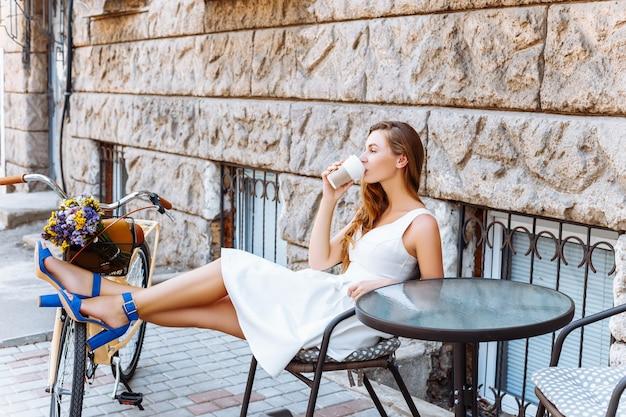 Красивая девушка пьет кофе на улице