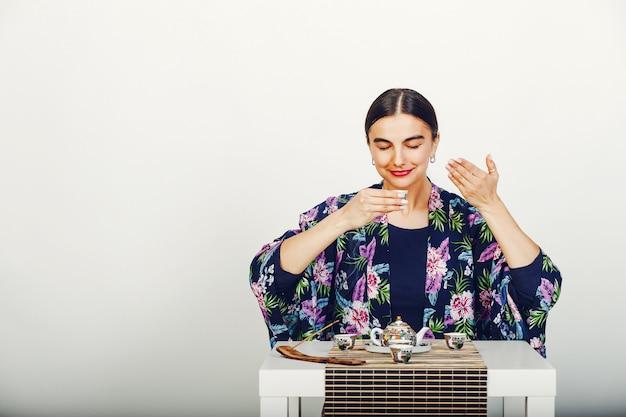 Красивая девушка пьет чай в студии