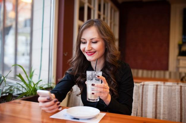 Красивая девушка пьет кофе и смотрит на свой телефон Premium Фотографии