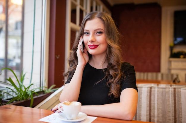 Красивая девушка пьет кофе и разговаривает по телефону