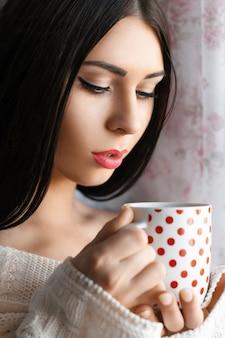 家でコーヒーを飲む美しい少女
