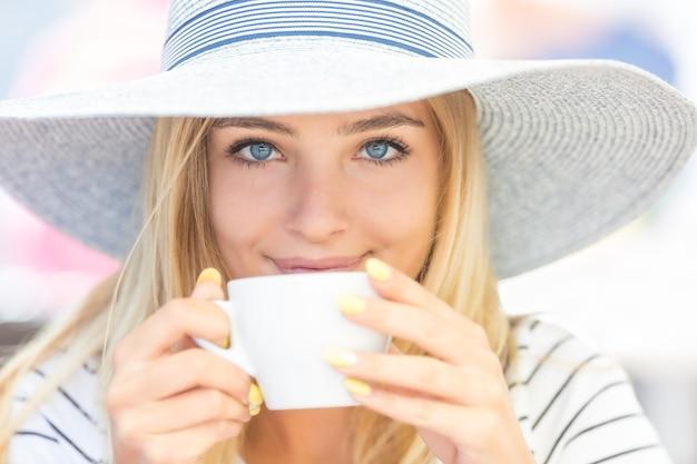 カフェテラスでコーヒーを飲む美少女。夏の肖像画の若い女性。