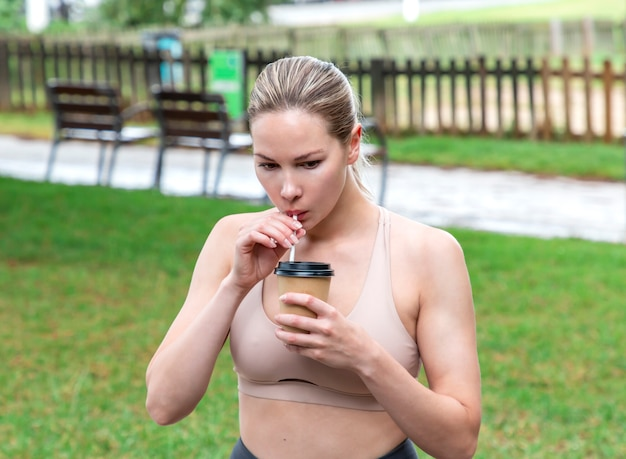 Beautiful girl drinking a drink from a cardboard glass in nature
