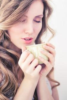 Красивая девушка, пить горячий кофе утром на белом фоне.