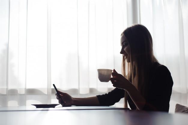 Красивая девушка пьет чай и с помощью мобильного телефона, сидя в кафе перед большим окном