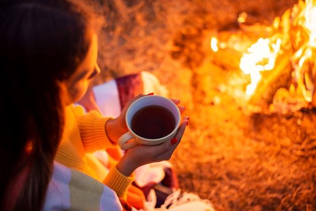 火のそばでお茶を飲む美少女