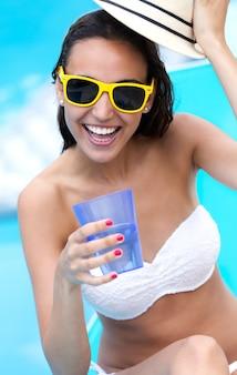 Красивая девушка питьевой воды в бассейне.