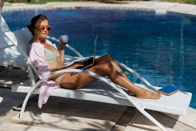 Красивая девушка пьет кофе у бассейна