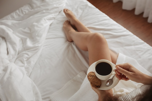 Beautiful girl drinks coffee with cookies bed