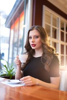 Красивая девушка пьет кофе