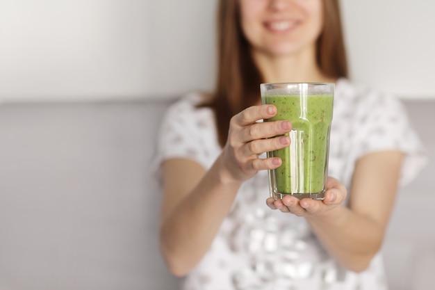 Красивая девушка пьет свежеприготовленный коктейль на кухне. смузи, свежеприготовленные из разных растительных ингредиентов на кухне. здоровое питание. выборочный фокус