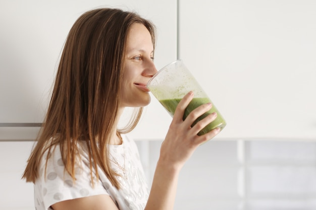 Beautiful girl drinks freshly prepared smoothie in kitchen. smoothies freshly made from assorted vegetable ingredients on kitchen counter. healthy eating. selective focus