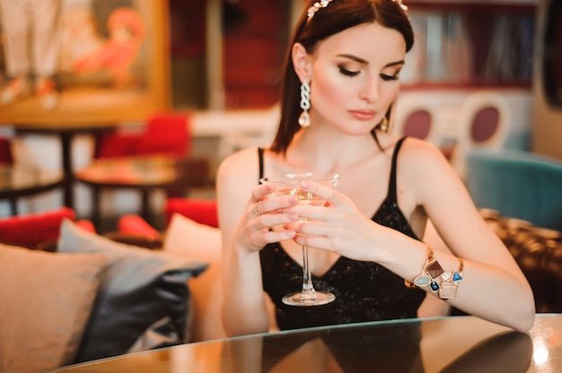A beautiful girl drinks martini in the hotel lobby and is waiting for her young boyfriend