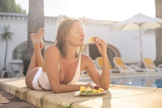 Красивая девушка ест свежие фрукты, лежа на выступе бассейна
